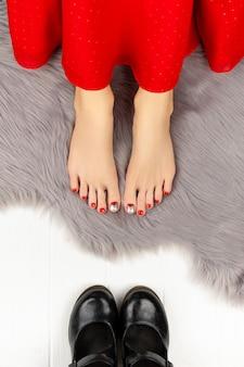 Vrouwelijke benen met rode nagels en schoenen op grijze pluizige deken.