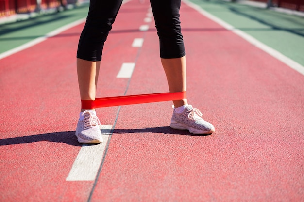 Vrouwelijke benen met rubberen weerstandsband. buitenopname