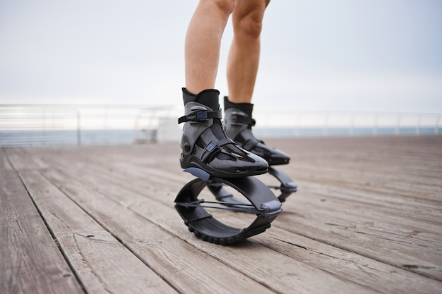 Vrouwelijke benen met schoenen springen op het strand