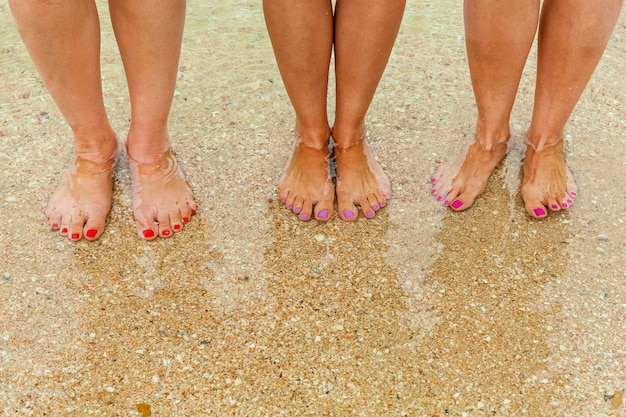 Vrouwelijke benen met veelkleurige nagels op de zeebodem zijn zichtbaar door het kristalheldere water