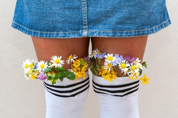 Vrouwelijke benen met verse bloemen in kousen