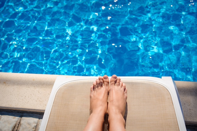 Vrouwelijke benen op een ligstoel op de achtergrond van het zwembad