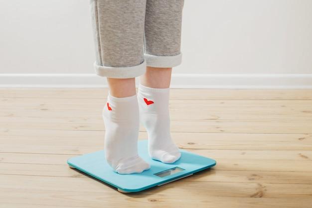 Vrouwelijke benen op elektronische weegschaal op een houten vloer