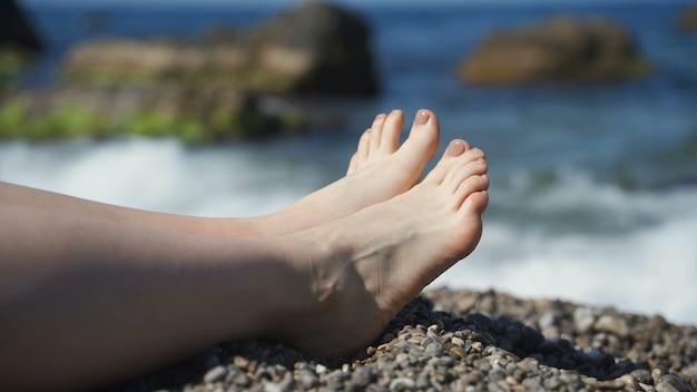 Vrouwelijke benen op het strand aan de zee van kiezelstenen. rust en ontspanning, slow motion, vakantie.