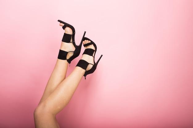 Vrouwelijke benen op hoge zwarte hakken op een roze achtergrond