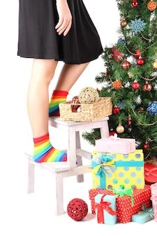 Vrouwelijke benen op houten ladder in de buurt van kerstboom en geschenken geïsoleerd op wit