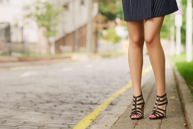Vrouwelijke benen op oude geplaveide bestrating, uitzicht vanaf de grond