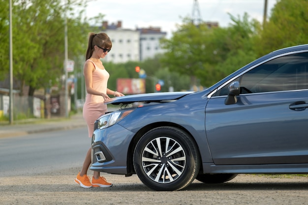 Vrouwelijke bestuurder die de motorkap van de auto opent en de kapotte motor op een stadsstraat inspecteert. voertuig storing concept.