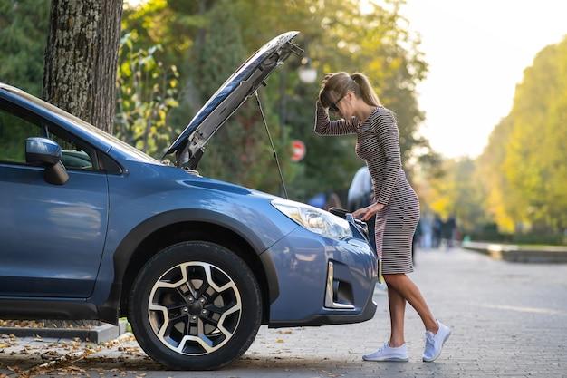 Vrouwelijke bestuurder die de motorkap van de auto opent en de kapotte motor op een stadsstraat inspecteert.