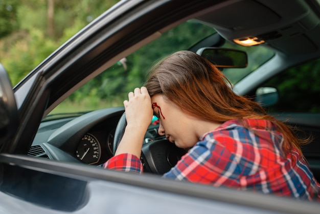 Vrouwelijke bestuurder met bebloede gezicht zit in de auto na een ongeval op de weg. auto-ongeluk, bloed op het gezicht van de vrouw. kapotte auto of beschadigd voertuig, auto-botsing op snelweg