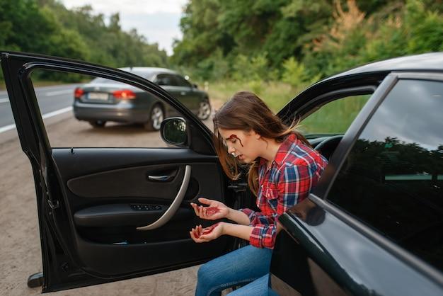 Vrouwelijke bestuurder met gebroken wenkbrauw na auto-ongeluk op weg. auto-ongeluk, bloed op het gezicht van de vrouw. kapotte auto of beschadigd voertuig, auto-botsing op snelweg