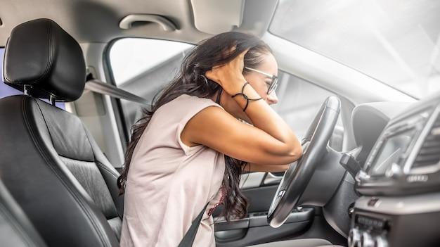 Vrouwelijke bestuurder met hoofdpijn of in wanhoop houdt haar hoofd met beide handen op de bestuurdersstoel.