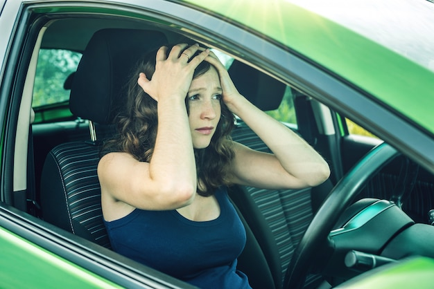 Vrouwelijke bestuurder zit boos achter het stuur van een auto