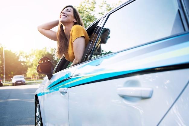 Vrouwelijke bestuurder zit in een auto en kijkt door raam