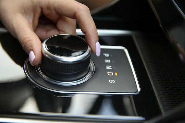 Vrouwelijke bestuurdershand schakelt de joystick van de automatische transmissie