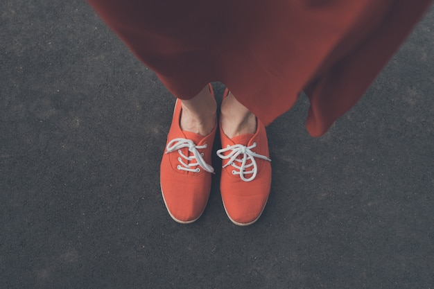 Vrouwelijke betaalt in rode sneakers op de stoep. uitzicht van boven