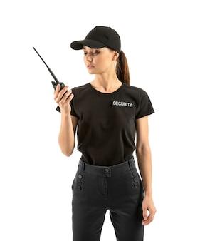 Vrouwelijke bewaker met draagbare radiozender op wit