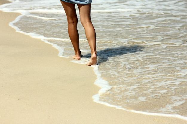 Vrouwelijke bezinksel voetafdrukken in het zand op het strand in de zomer