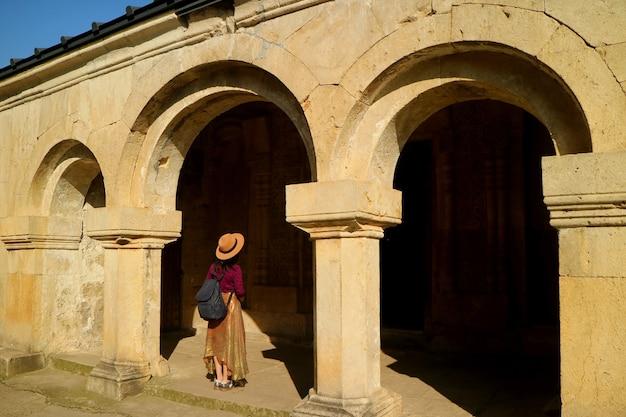 Vrouwelijke bezoeker bij de ingang van een st. george-kerk in het gerati-klooster