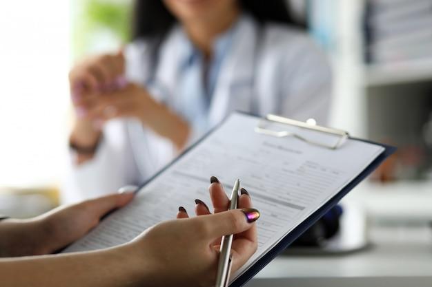 Vrouwelijke bezoeker die geneeskundedocumenten invult
