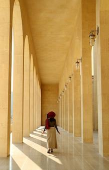 Vrouwelijke bezoeker die in de marmeren gang loopt