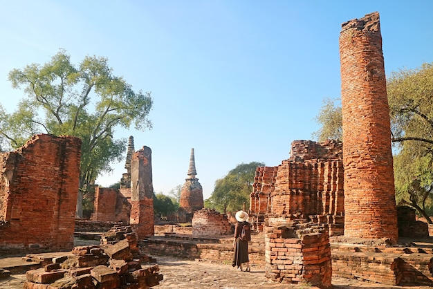 Vrouwelijke bezoeker die ruïnes onderzoekt in de wat phra si sanphet-tempel in het historische park ayutthaya, thailand
