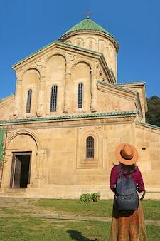 Vrouwelijke bezoeker kijken naar middeleeuwse kerk in gelati klooster in kutaisi city, georgia