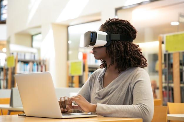 Vrouwelijke bibliotheekgebruiker die virtuele video bekijkt