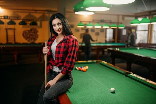 Vrouwelijke biljartspeler met cue vormt aan de tafel met kleurrijke ballen. vrouw speelt amerikaans poolspel in de sportbar