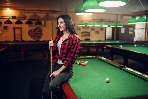Vrouwelijke biljartspeler met cue vormt aan de tafel