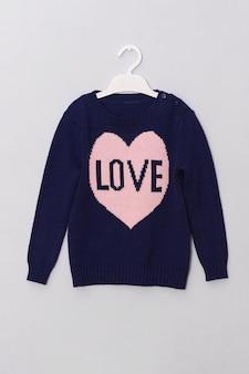 Vrouwelijke blauwe wollen trui met patroon roze hart en opschrift liefde op hanger.