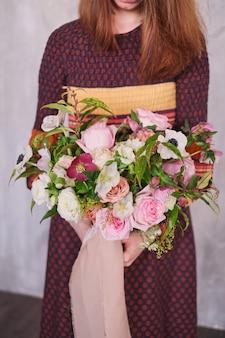 Vrouwelijke bloemist bedrijf bloeiende bloemen boeket van pastel anjers en eucalyptus