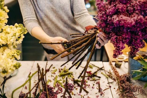 Vrouwelijke bloemist boeket van lila in bloemenwinkel maken