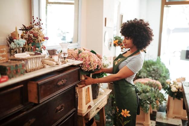 Vrouwelijke bloemist die bloemen in bloemenwinkel schikt