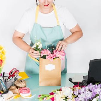 Vrouwelijke bloemist die bloemen in document zak schikken