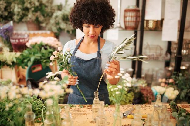 Vrouwelijke bloemist die bloemen in glasvaas schikt