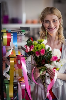 Vrouwelijke bloemist die een bloemboeket voorbereidt