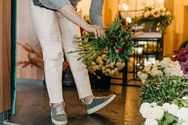 Vrouwelijke bloemist die een boeket bij bloemenwinkel maakt