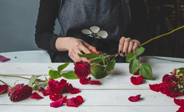 Vrouwelijke bloemist die een boeket rozen maakt