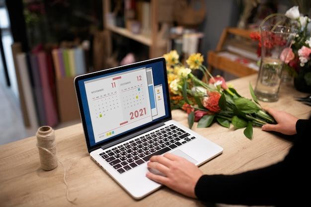 Vrouwelijke bloemist die een laptop gebruikt op het werk