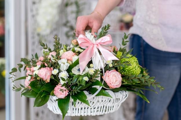 Vrouwelijke bloemist die een mooi boeket rozen in witte mand