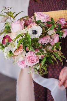 Vrouwelijke bloemist die een vers gemaakte bloeiende bloemen boeket van pastel tegen een grijze muur.