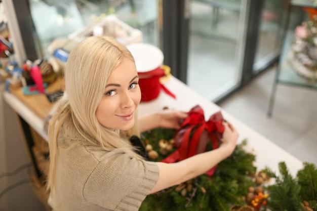 Vrouwelijke bloemist die kerstkrans maakt in bloemenwinkel