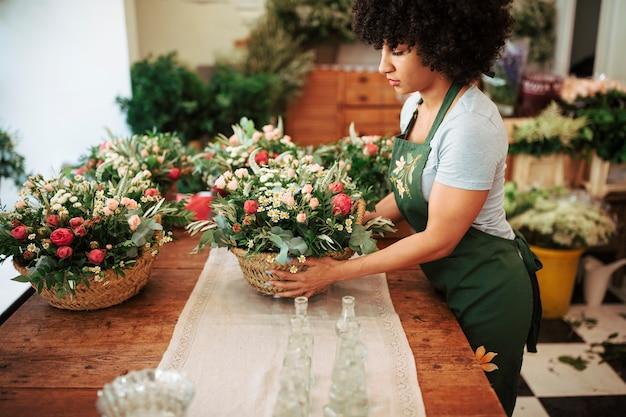 Vrouwelijke bloemist die mand van bloemen op houten bureau schikken