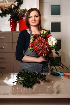 Vrouwelijke bloemist die met bloemen werkt