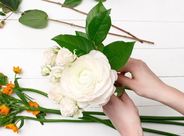 Vrouwelijke bloemist die mooi boeket maken bij bloemwinkel