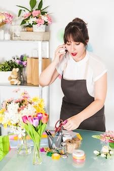 Vrouwelijke bloemist die op cellphone in bloemenwinkel spreekt