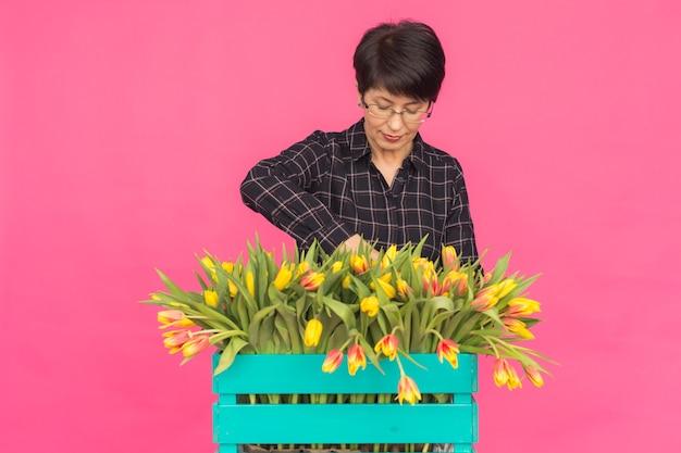 Vrouwelijke bloemist die op middelbare leeftijd blauwe houten doos tulpen op roze achtergrond houden