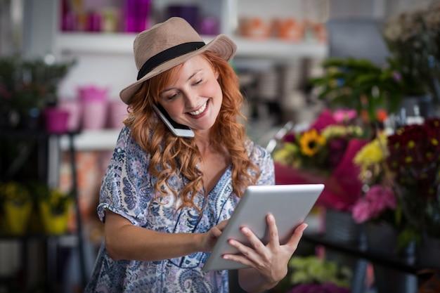 Vrouwelijke bloemist die op mobiele telefoon spreekt terwijl het gebruiken van digitale tablet