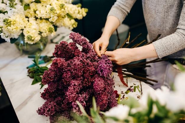 Vrouwelijke bloemist die paars lila boeket maakt